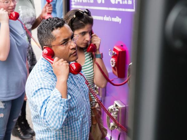 "Image of participants engaging in interactive experiences on the ""Check Your Blind Spots"" bus tour include a phone bank, ""Wake Up Call: Listen to Someone Else's Reality."""